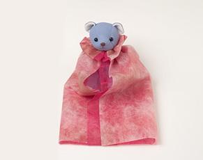 (6)ぬいぐるみが座ったままの状態で、足先に扇状に広がった包装紙の左右を合わせて、まっすぐになるように折る。このとき、ぬいぐるみの前側の包装紙が少し開き気味