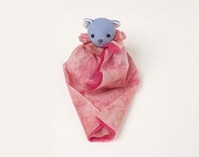 (7)さらに、包装紙の前方手前の角を斜めに折る。前段階で、ぬいぐるみの前側の包装紙が少し開き気味になっていた場合は、斜めに折るときに、内側にたくし込